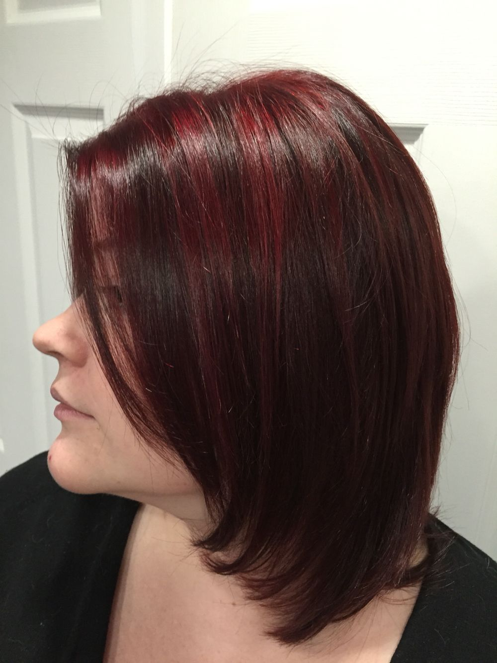 Long layered bob with cherry red highlights on natural dark brown