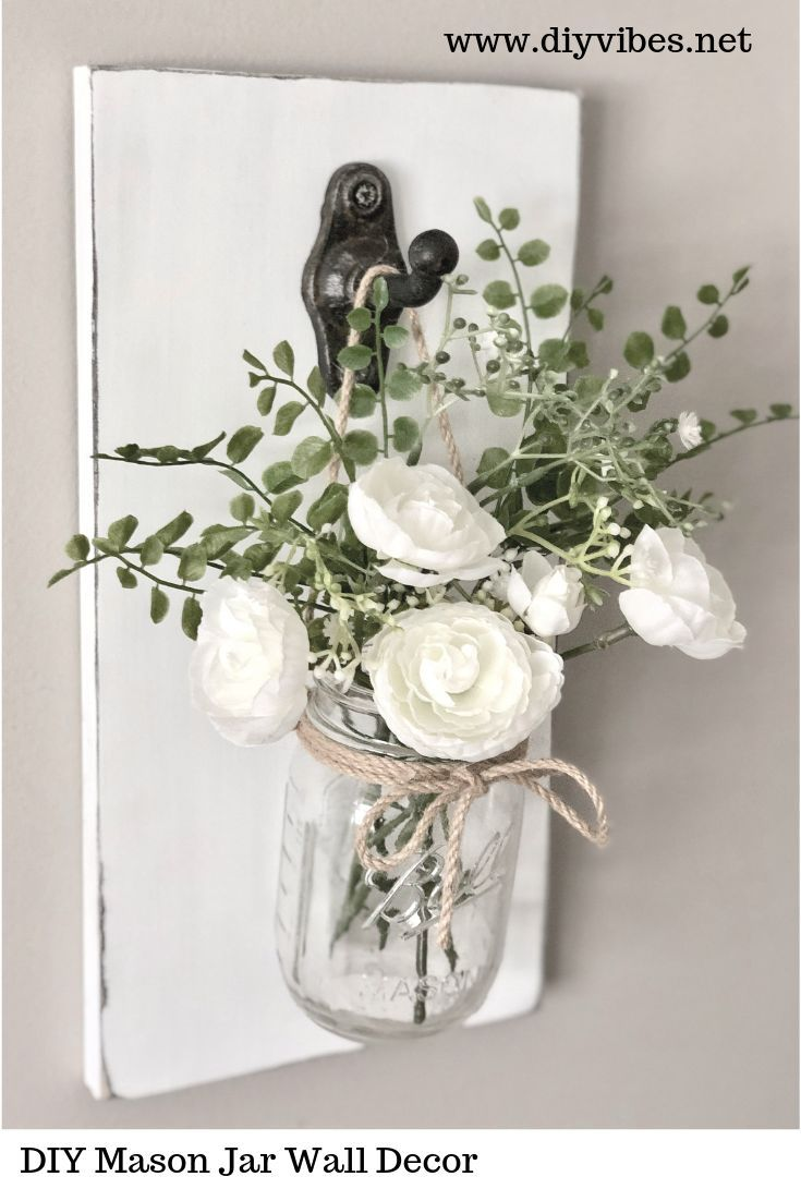 This adorable, rustic DIY mason jar wall decor will brighten up any room. Change out the flowers for all seasons to give it a different look. See how to make it at www.diyvibes.net. #masonjarcrafts #masonjarideas #masonjarwalldecor #masonjarwallsconce #farnhousedecor