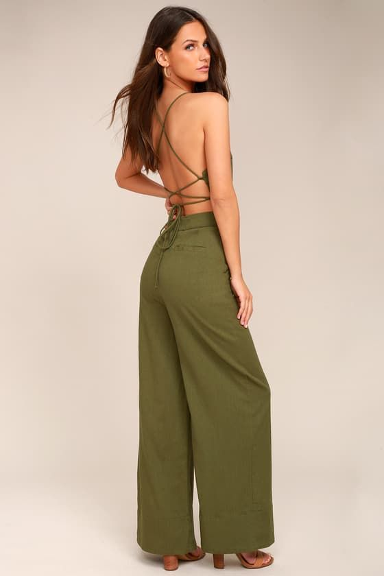Kick up some sand on the seaside with the Beach Day Olive Green Backless Jumpsuit! Breezy, cotton-linen blend fabric forms this cute and casual jumpsuit with a button-up bodice, and skinny straps that lace-up atop an open back. Banded waist tops relaxed pant legs with diagonal front pockets and welt back pockets.