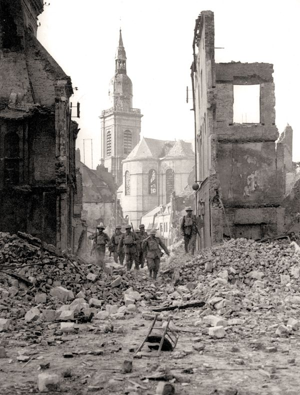Soldiers pick their way through the ruins at Cambrai, 1918.  PHOTO: ARCHIVES OF ONTARIO—C224-0-0-10-37