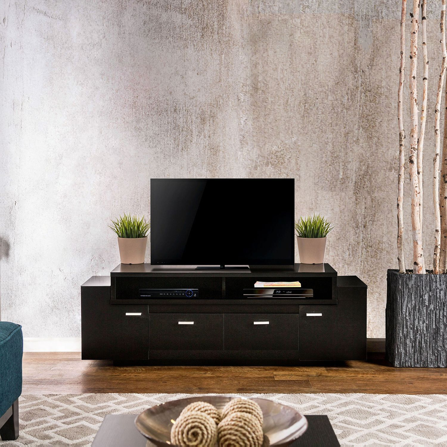 Available in two finishes, this 60-inch TV stand is a sure fit for any living space. The spacious shelving compartments and convenient cabinet and drawers pair wonderfully to create the ultimate entertainment center.