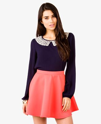 A crepe woven blouse featuring an eyelet Peter Pan collar. Round neckline. Shirred shoulders. Darted bust. Long sleeves with button cuffs. Buttoned keyhole back. Unlined. Lightweight.