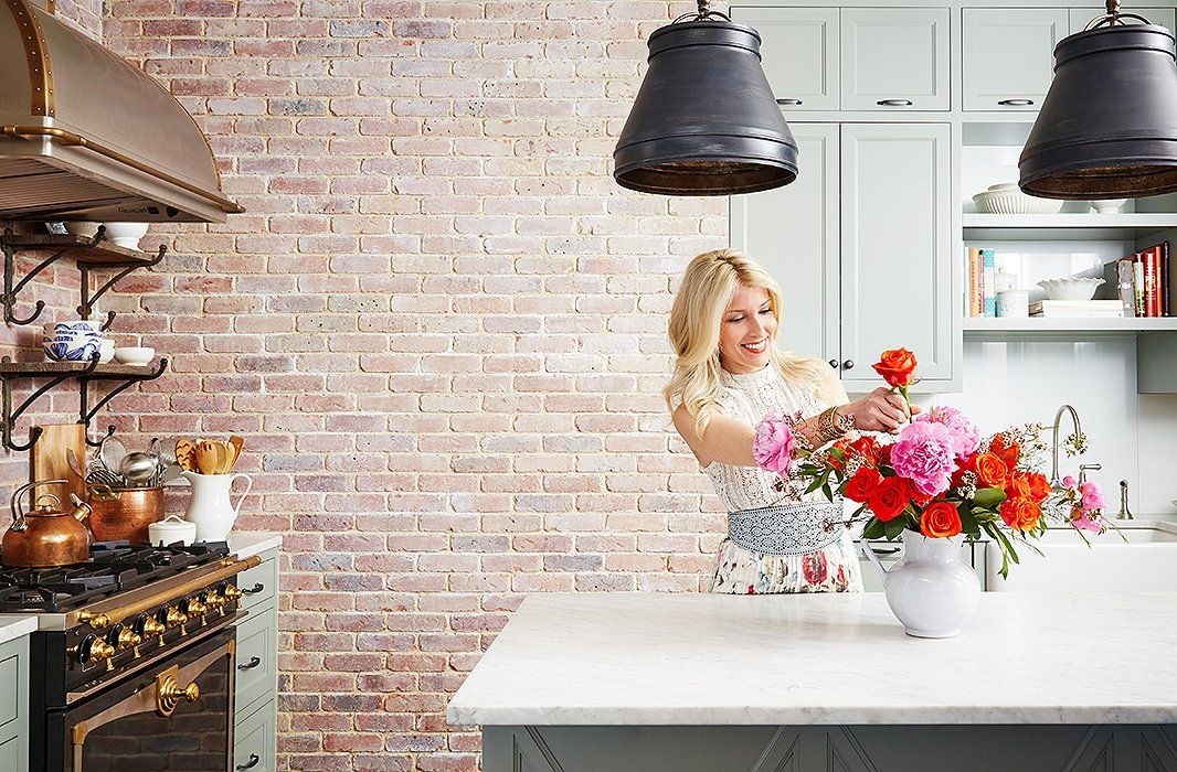 Interior designer Jenny Wolf arrangements bright pink and red blooms in her finished farmhouse-inspired kitchen.
