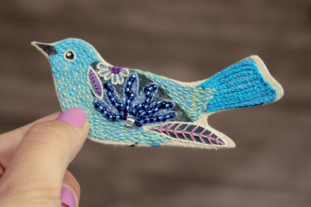Embroidered and beaded bird brooch by Geninne