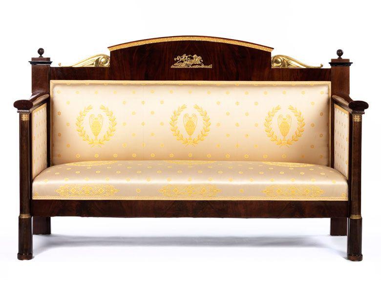 Furniert in ausgesuchtem Mahagoni, partiell ebonisiert und goldgefasst sowie vergoldete Bronzeapplikationen. Armlehnen geschlossen, Sitzfläche und Rückenlehne ...
