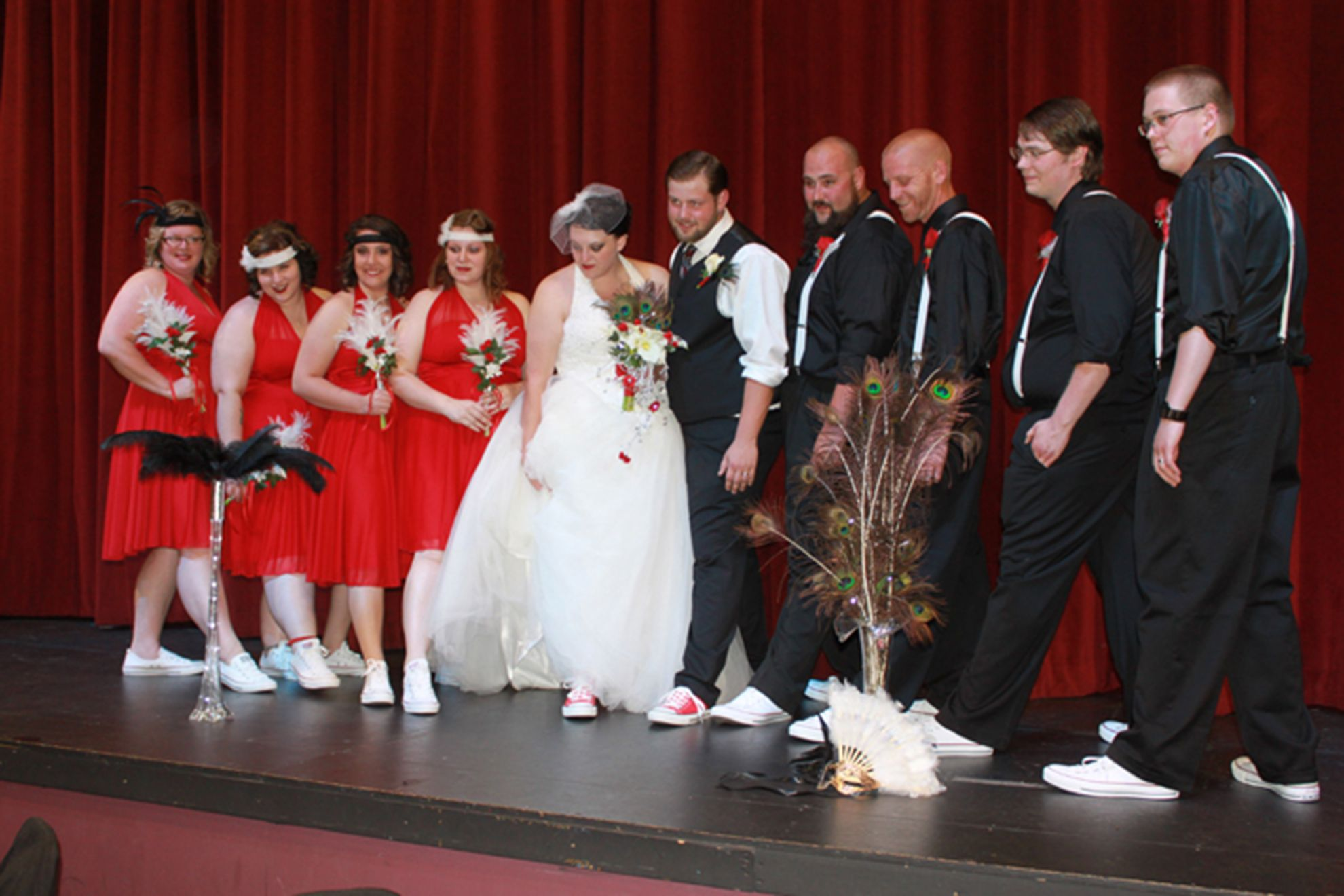 Bride and groom and wedding party showing off Converse shoes on stage at  red 9d9b74abc