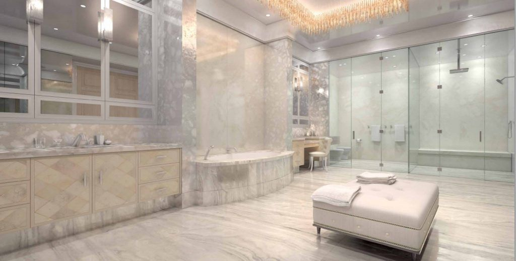 This NYC bathroom has marble flooring, glass enclosed shower, metallic cabinetry, tufted ottoman, hanging light fixture, and oval bathtub.