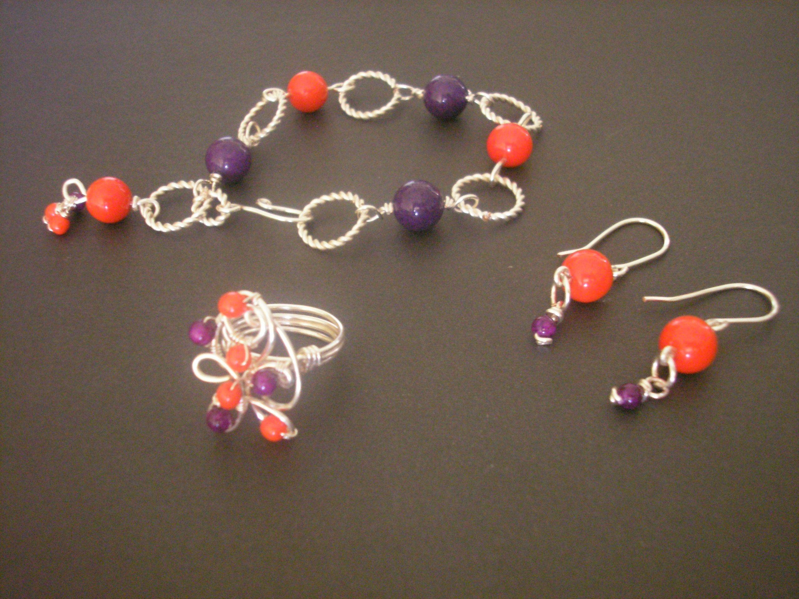 juego de pulsera , anillo y aretes rojos y morados.. en alambrismo