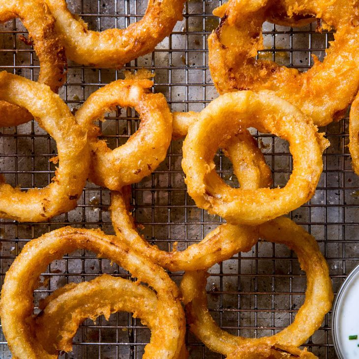 BA's Best Onion Rings Recipe with sweet onion, buttermilk, cornmeal, baking powder, smoked paprika, all-purpose flour, kosher salt, club soda, lager, vegetable oil, buttermilk ranch dressing