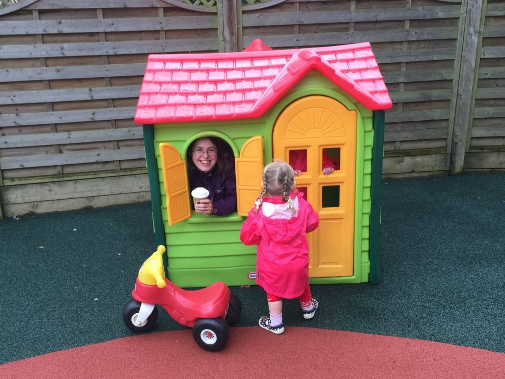 Mummy Taking Shelter From The Rain Inside A Little Tikes Playhouse