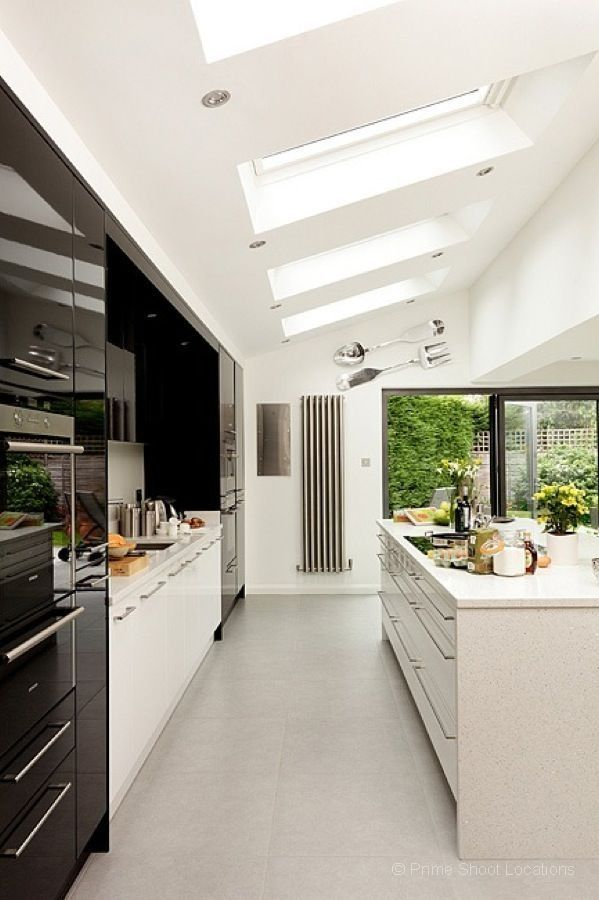 A Striking Contemporary Minimalist Kitchen With Central Island And Sleek In  Design. The Kitchen Has An Open Plan Dining Area And Has A Bright Sunny  Aspect ...