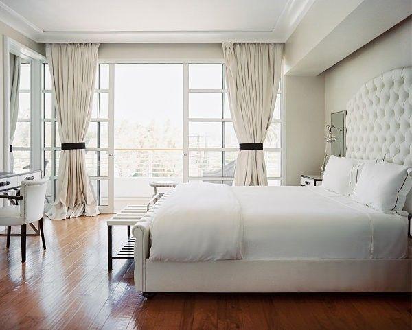 Một chút đen buộc ở rèm cùng với sàn nhà bằng gỗ tạo nên sự cân bằng cho căn phòng toàn màu trắng này.
