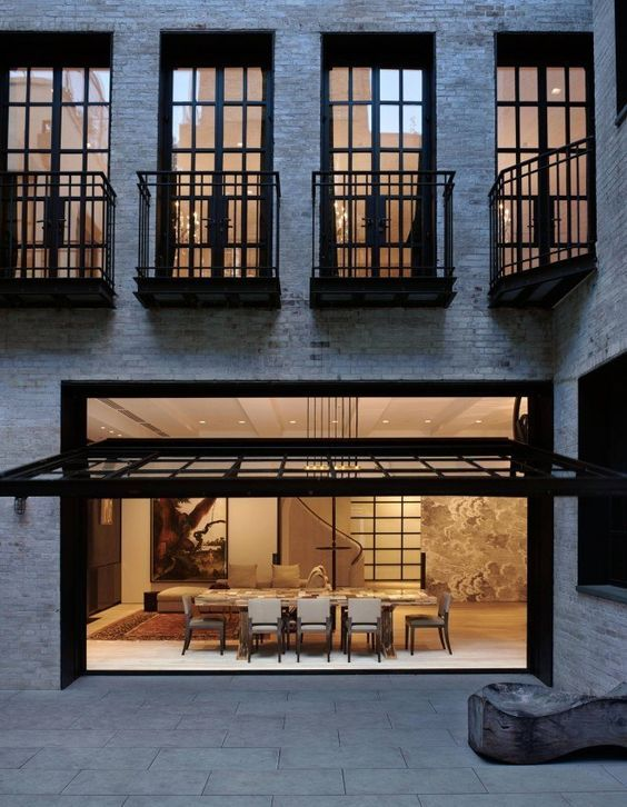 black frame garage door that opens a dining space to the outside ...