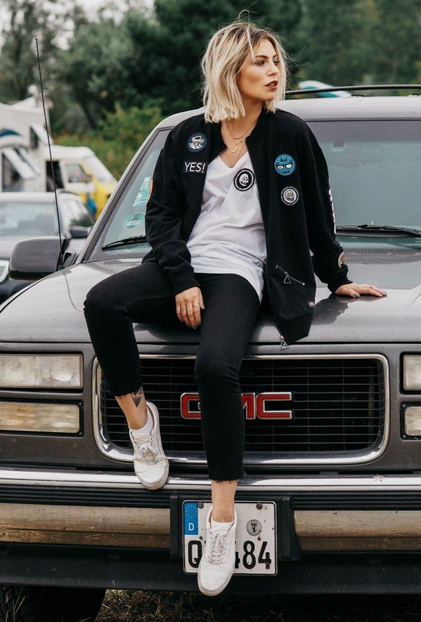 frayed jeans with bomber jacket with brooch and sneakers