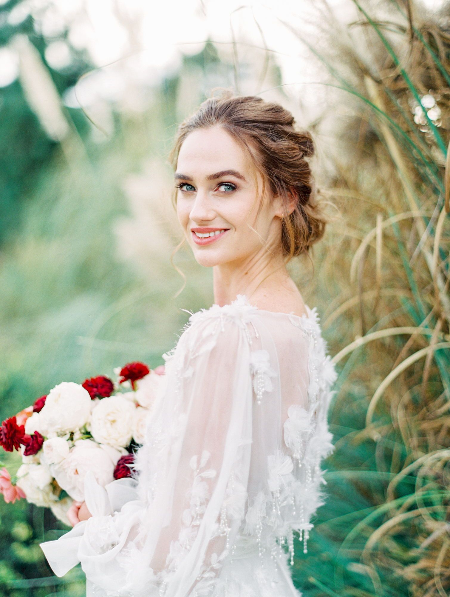 629f1729 Bride with soft curled updo and natural makeup wearing long sleeve floral  and feather Marchesa gown ...
