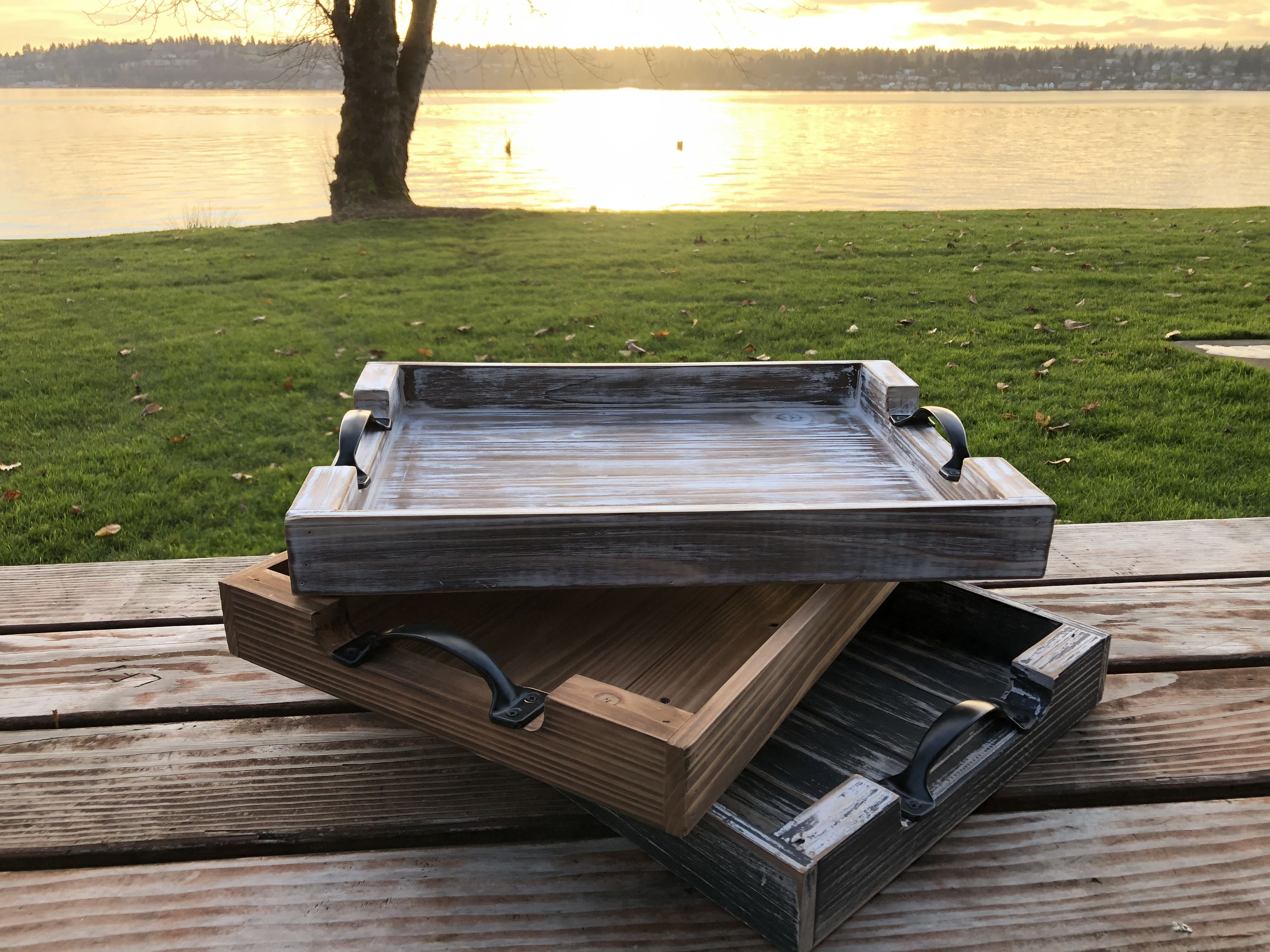 """The """"Abigail"""" trays stacked up in a staggered manner with a beautiful sunset and lake in the background.       #sunset #sunsetphotography #lakelife #lake #servingboard #servingplatter #servingtray #tray #traytable #woodtray #ottomantray #cozy #lifeisgood #lifeisbeautiful #loveyourselffirst #loveyourlife"""