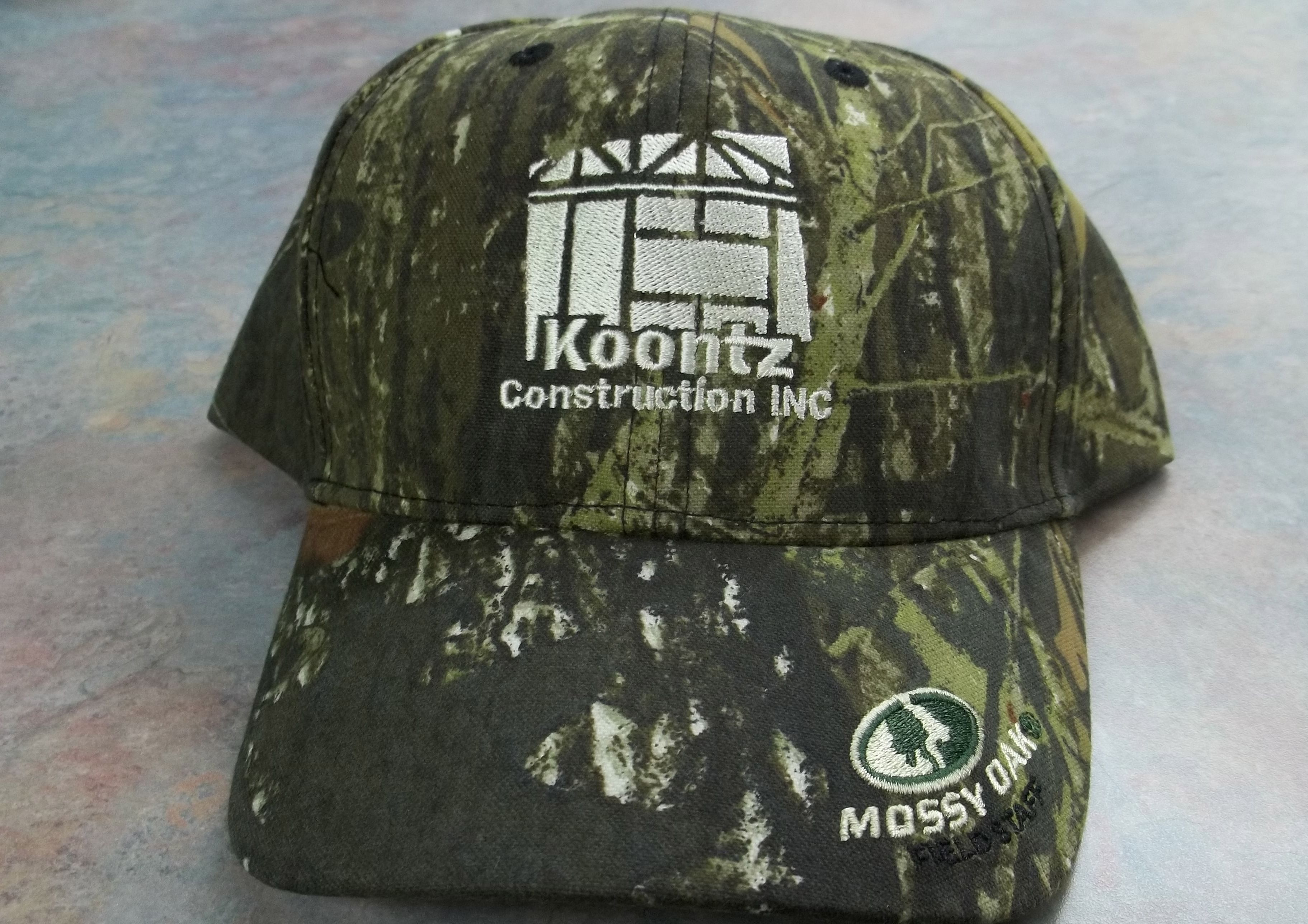 Koontz Construction Logo on Mossy Oak Cap.  Embroidery by Top It Off.