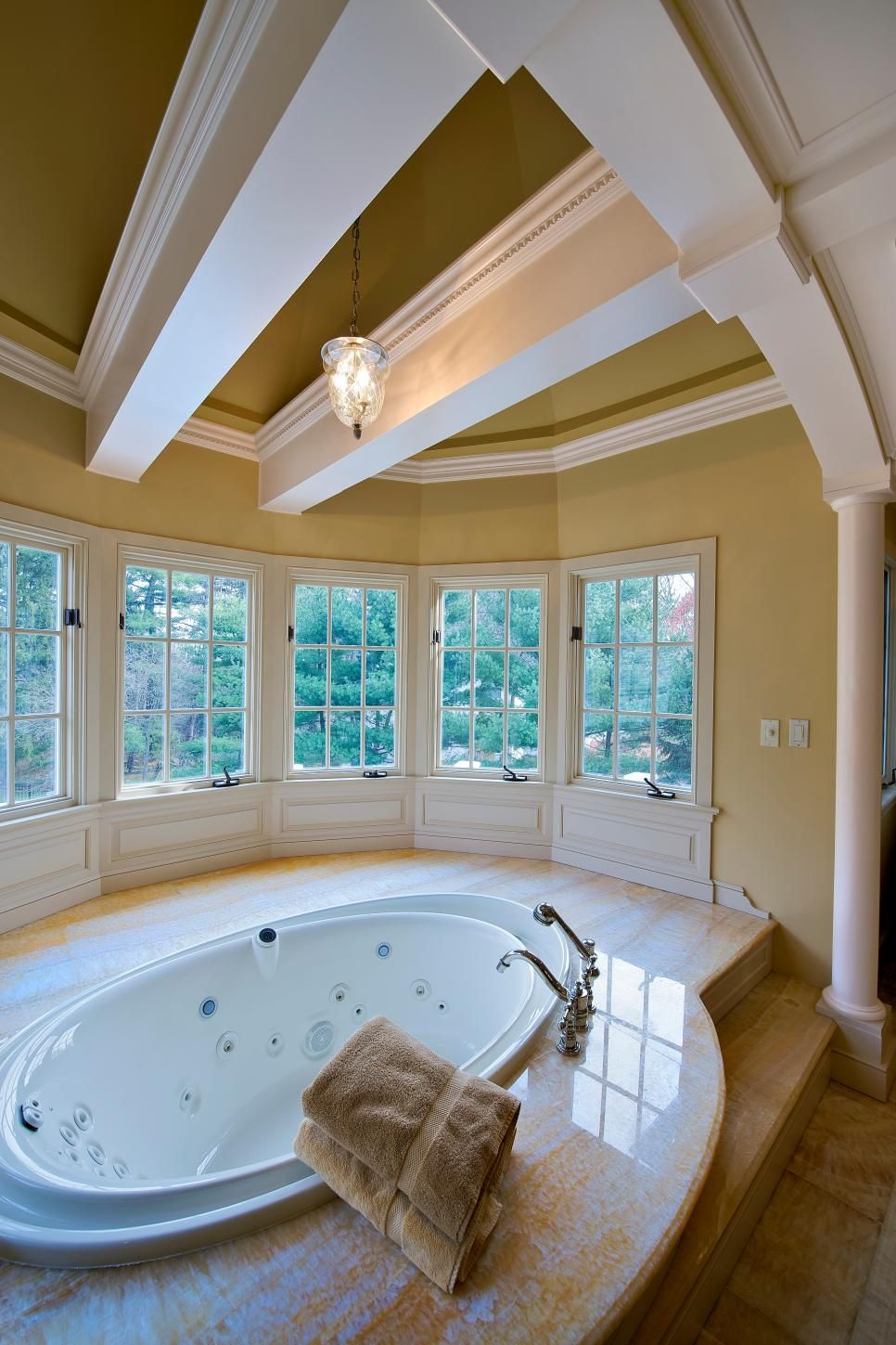 A luxurious spa bathtub set in marble and surrounded by curved ...