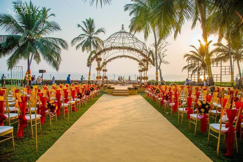 Red and gold wedding setup with an open air wrought iron cut out red and gold wedding setup with an open air wrought iron cut out mandap decorated with fresh flowers junglespirit Image collections