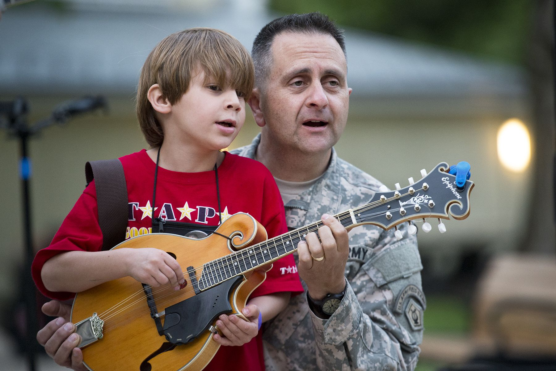 Jason Thomas, 6, plays mandolin with the help of Army Master Sgt. John Lamirande of the during an event for family members from the Tragedy Assistance Program for Survivors at the Pentagon, May 22, 2015. Lamirande is a member of the U.S. Army Field Band's Six String Soldiers. DoD photo by EJ Hersom