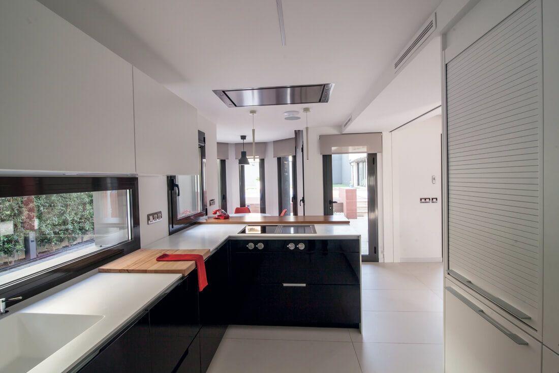 Una luminosa cocina en blanco y negro con península y office
