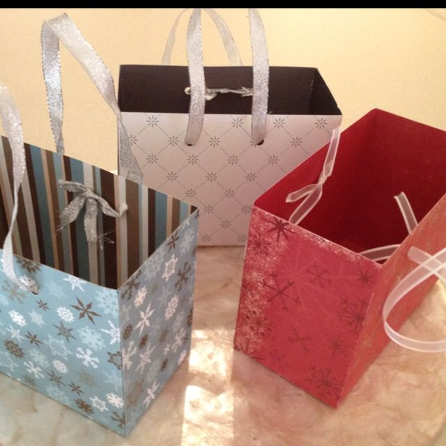 """Gift boxes made out of 12x12 scrapbook paper and ribbon. Fold paper sides at 3"""" and 9"""". Turn paper and fold opposite direction at 7.5"""" and 4.5. You should have crease lines that measure 3""""- cut those. Fold tabs inward and assemble with glue."""