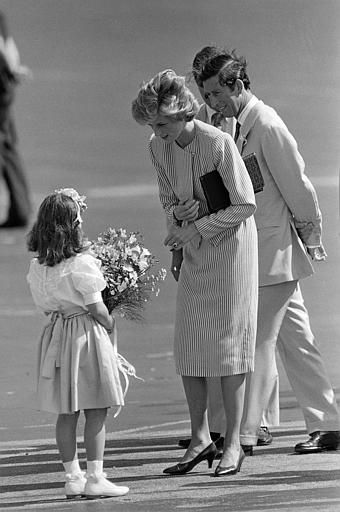 1985-11-12 Diana receives a bouquet of flowers from 7-year-old Tara Sansbury on arrival at West Palm Beach International Airport in Florida