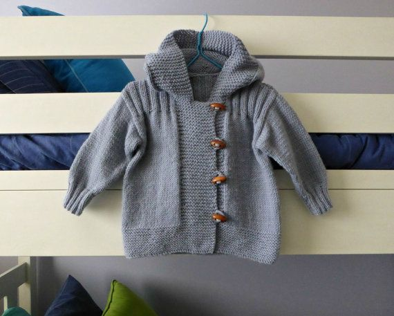 Hand knitted baby dungarees with  striped patch pockets detail with over shoulder wooden fastenings also available with matching cardigan.