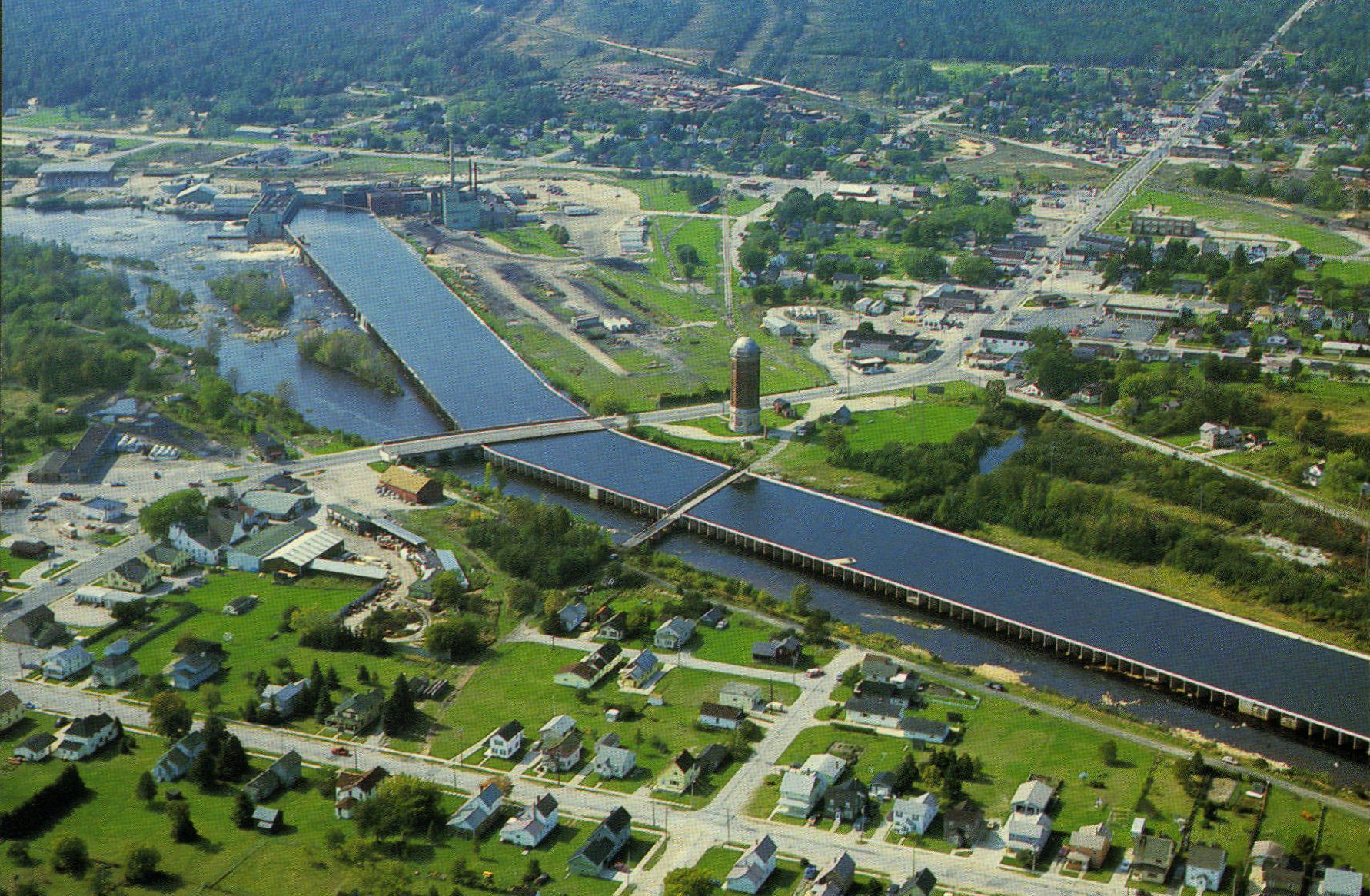 Manistique, MI: This view shows the reservoir of the Manistique River which supplies water to the Paper Mill.  Also the famous Siphon Bridge and historic water tower can be seen in the center.  Manistique is a leading vacation and resort city in Michigan's Upper Peninsula.  Photo by John Penrod (postcard).