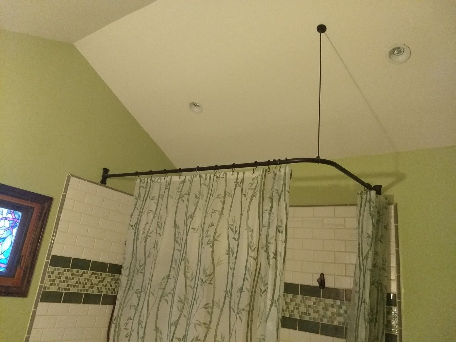 A Corner Shower Rod With A Sloped Rod Support On An Angled Ceiling