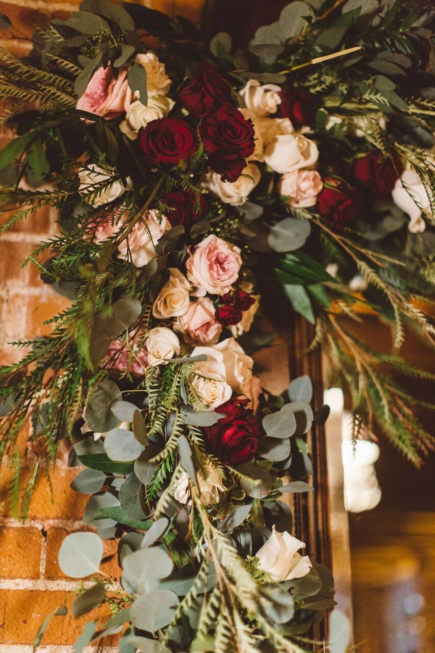 wedding arch draped in pink and burgundy flowers Wedding