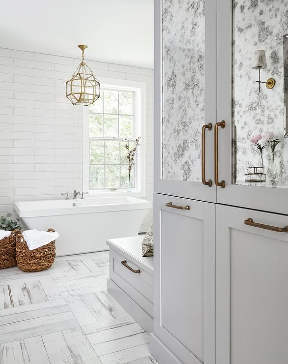 White And Gray Distressed Floor Tiles Lead Past Antique Mirrored Cabinet Accented With Br Pulls To