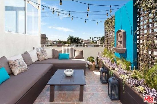 Patio idea, love the bold blue color and hanging water fountain!