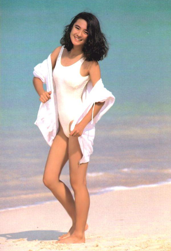 白い水着に白いパーカーで海辺を歩くホクロのある藤谷美紀