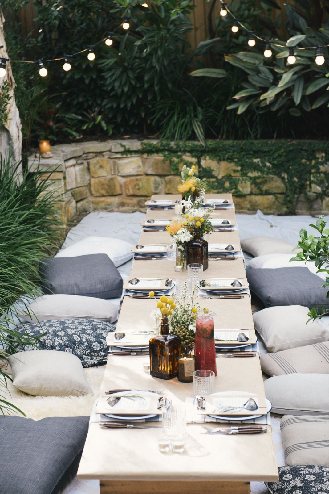 The Long Picnic Table Setting With Floor Cushions, Rugs And Festoon  Lighting, Just Crying