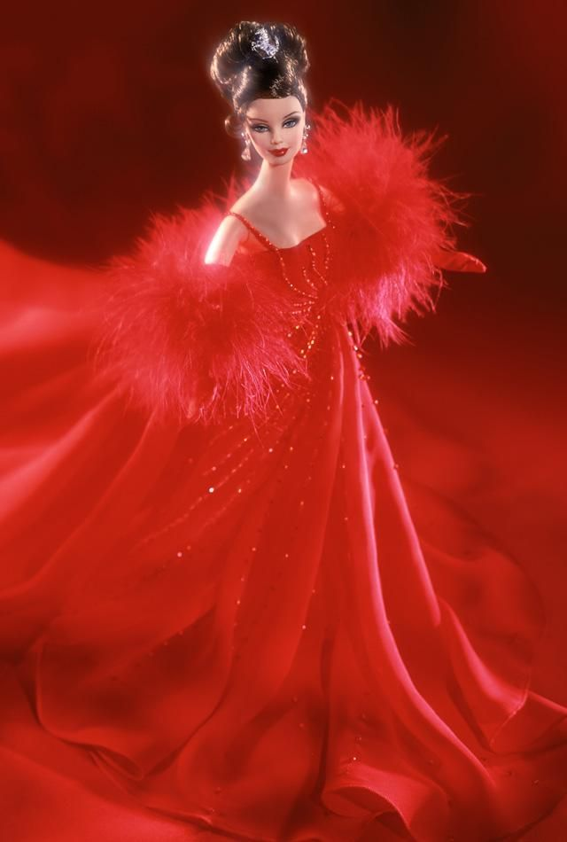 Ferrari Barbie® Doll. Barbie® doll pays tribute to her favorite car, Ferrari, wearing a sophisticated red evening ensemble. The gown is exquisite down to the last detail, from the delicately beaded straps to the dramatic, flowing skirt. To accessorize the look, Barbie® wears a soft stole trimmed with marabou, long red gloves and Swarovski® crystal drop earrings. Her brown hair is styled in an intricate updo and finished with a silvery hair ornament in the shape of the Ferrari...