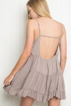Jada Dress- this dusty lavender tiered dress gives the model a more full shape .The looser fit makes the model appear much larger then she actually is , but the lack of sleeves and the bare back cutouts brings the design forward and makes the style more casual  .