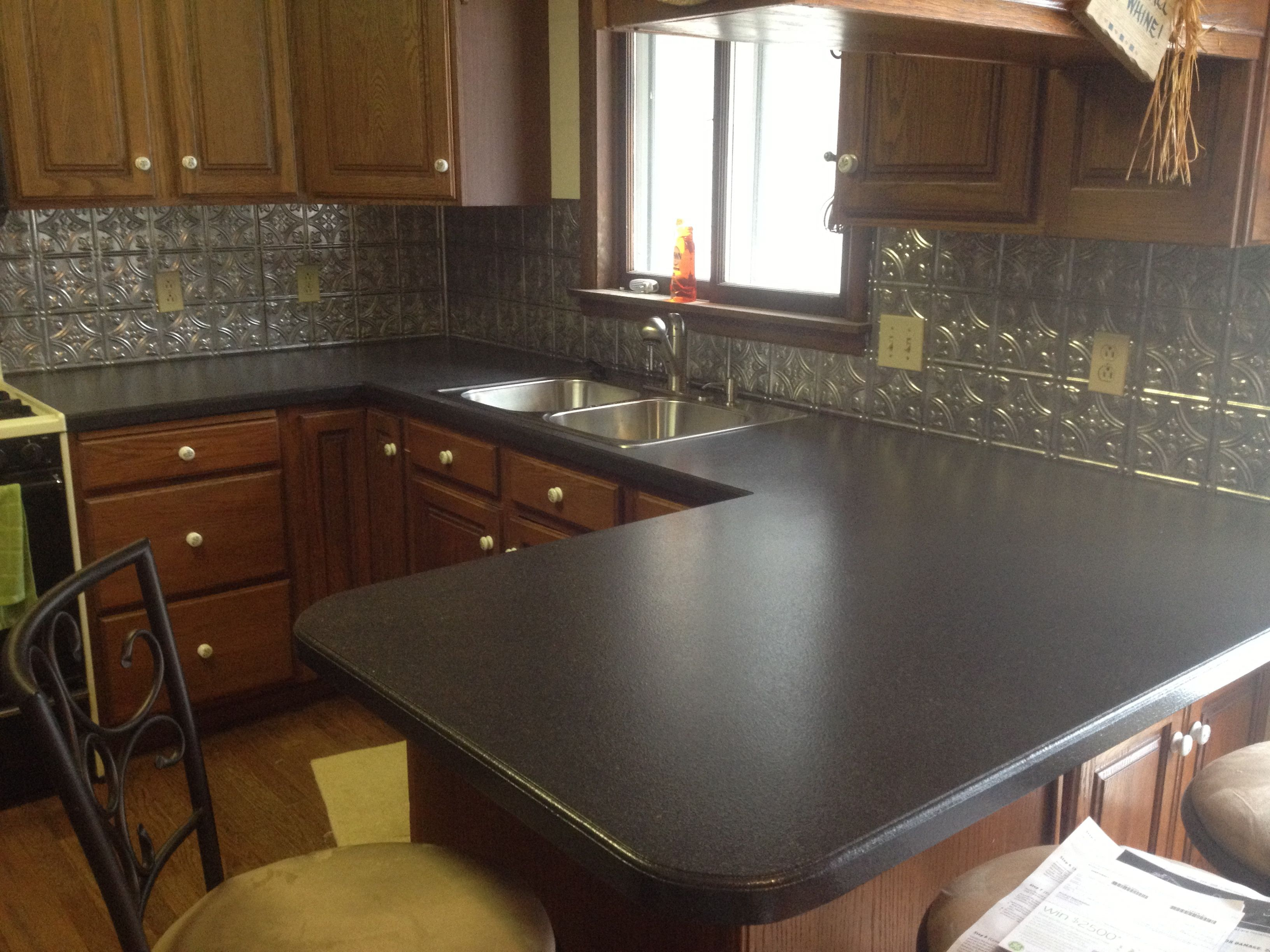 Black Corian Vs Granite Countertop With Tile Backsplash And Glass Window  Plus Wood Cabinets For Kitchen Design