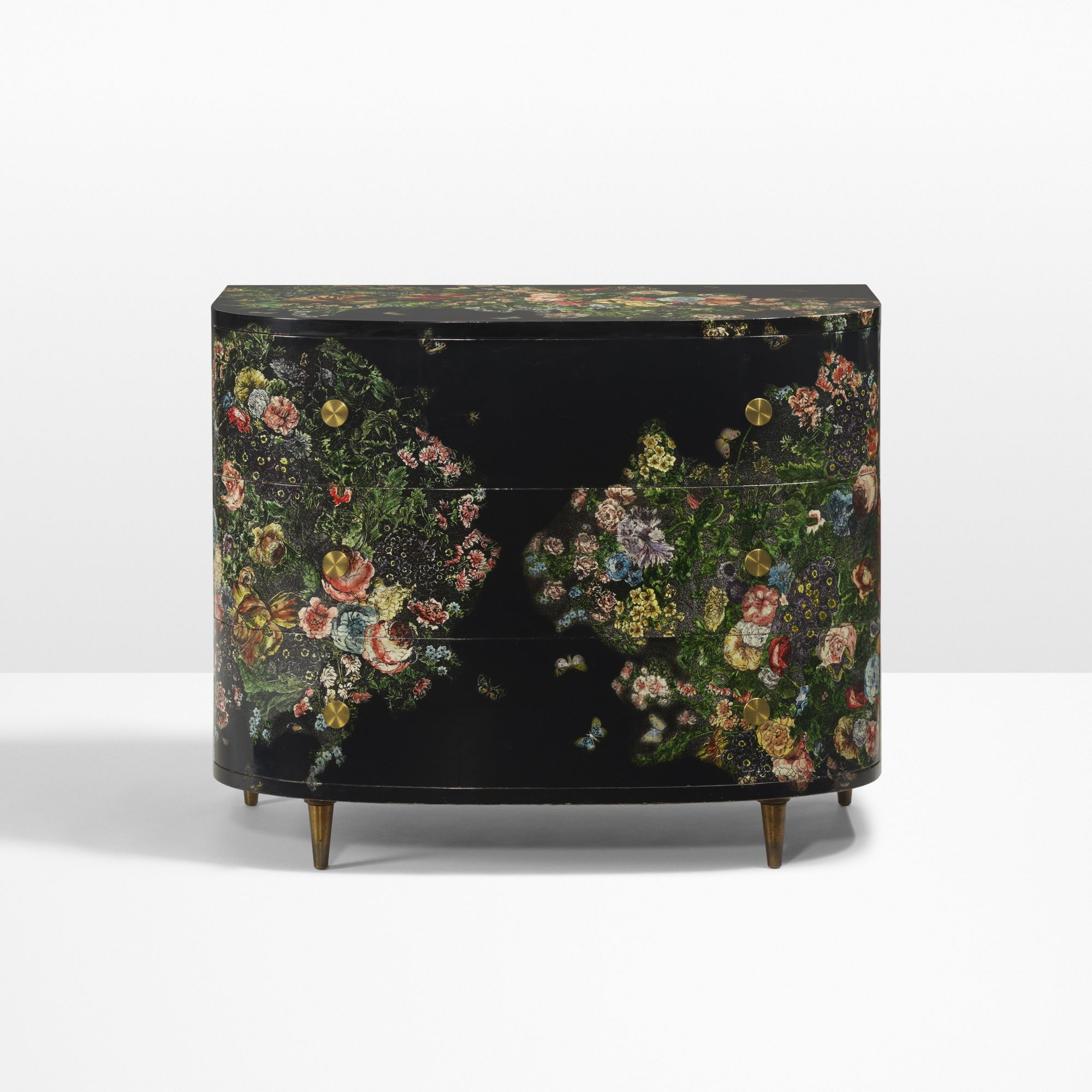 Lot 27: Piero Fornasetti. Fiori nella notte cabinet. 1955 / c. 1975, hand-painted and lithographic transfer-printed wood, brass. 39¾ w x 22 d x 32½ h in. estimate: $30,000–40,000. Cabinet features three drawers. Signed with applied metal manufacturer's label to drawer: [Fornasetti Milano]. This work has been reviewed by Barnaba Fornasetti. Provenance: Private Collection, Como, Italy   Acquired circa 1985 by the present owner