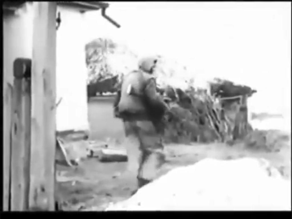 SS trooper moving through a village, Kharkov 1943