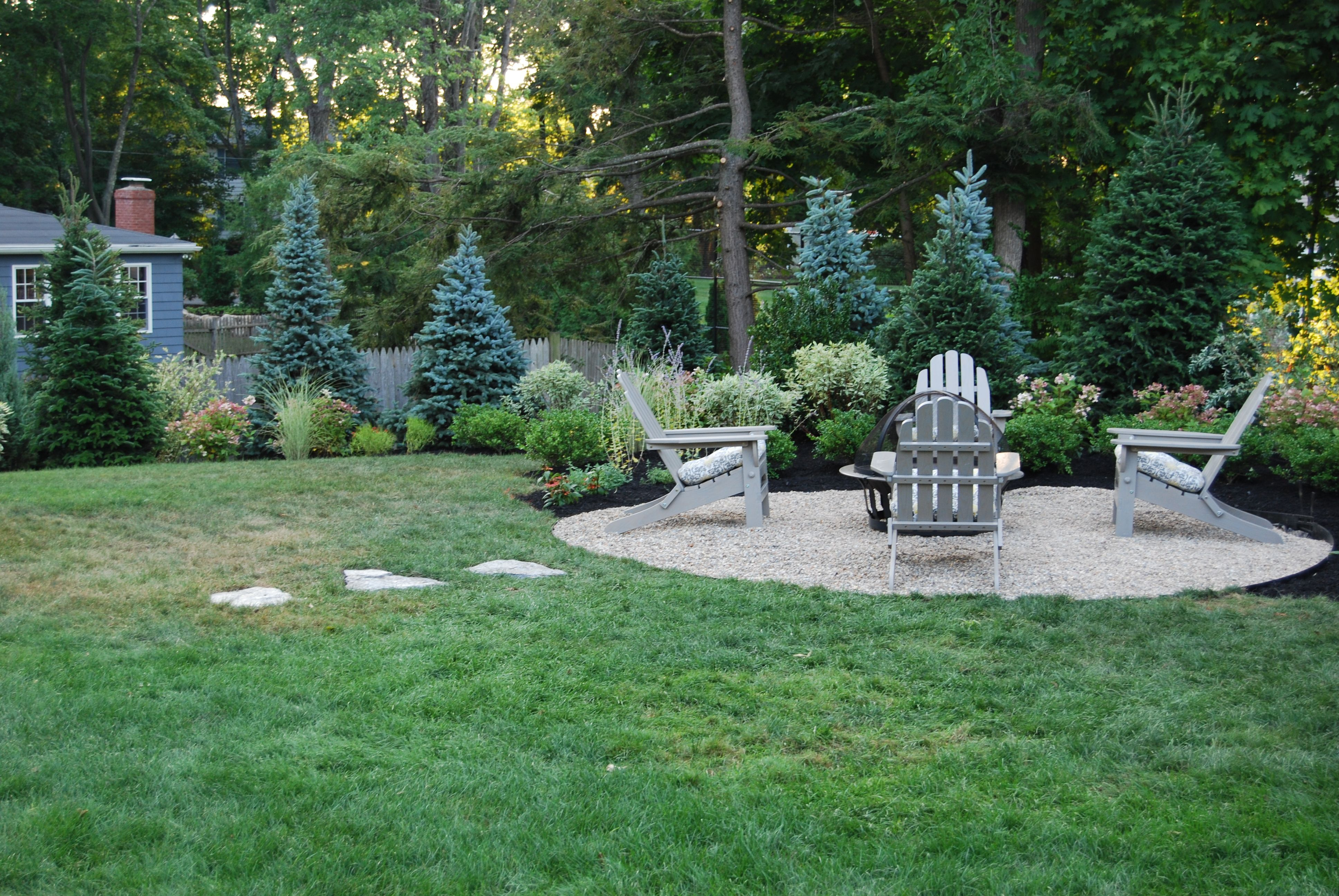 a gravel fire bowl area surrounded by evergreens mixed shrubs and
