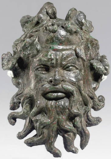 A ROMAN BRONZE SILENUS MASK APPLIQUÉ   CIRCA 1ST CENTURY A.D.   The companion of Dionysus with a fillet of ivy and berries along his bald pate, his bulging almond-shaped eyes deeply set below his furrowed, overhanging brow, with a snub nose and rounded cheek bones, his beard and mustache formed of thick radiating wavy locks  4 in. (10.2 cm.) high