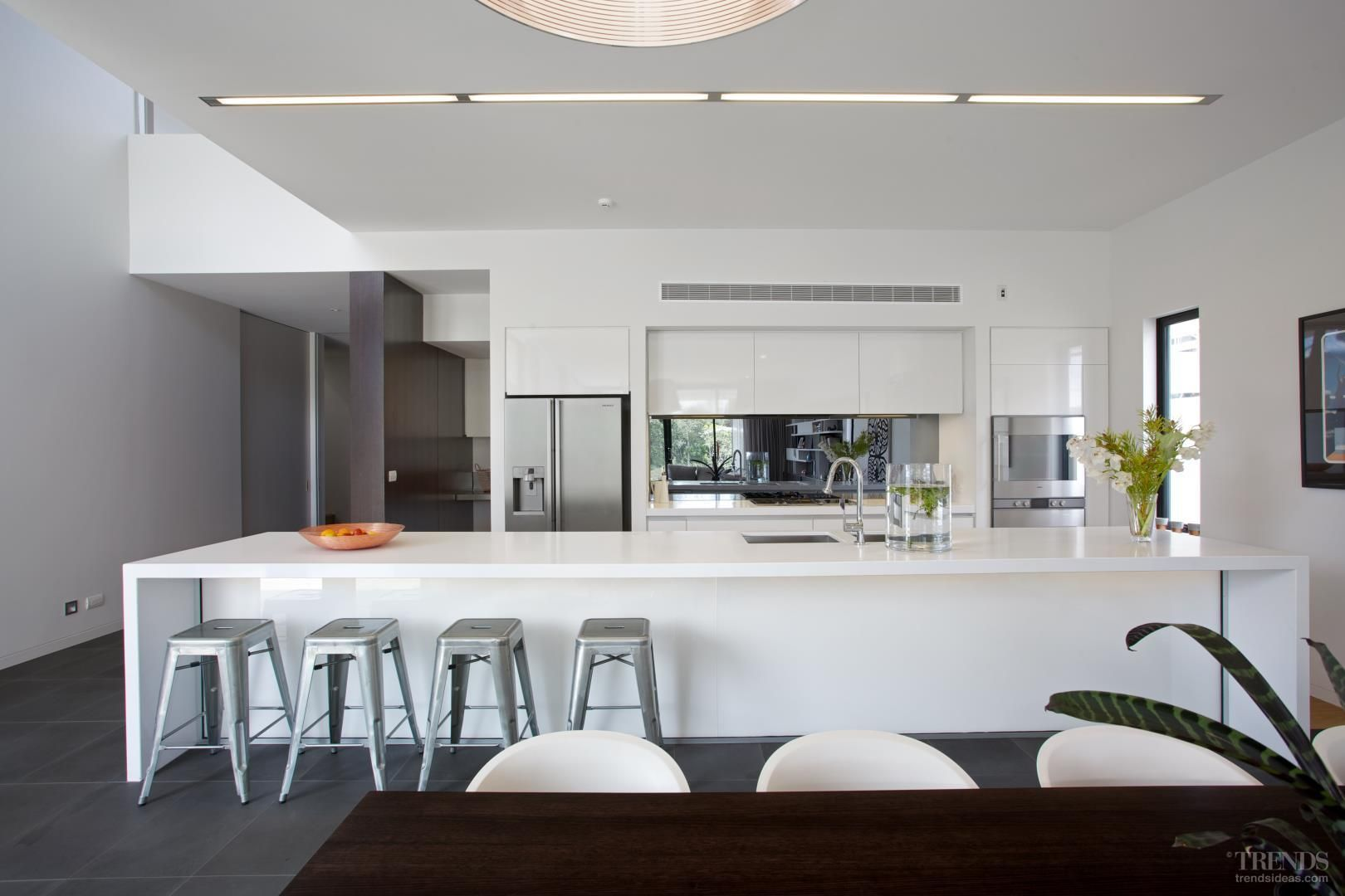 Sleek white kitchen design in new house with 5m-long island ...