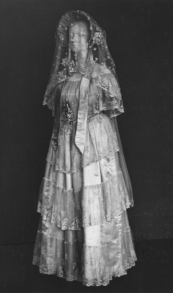 1848 White silk satin wedding dress with overdress of embroidered flounced net lace, white satin bonnet, a bonnet-veil of applied bobbin lace motifs on net, a handkerchief of white embroidered cambric, a pair of garters of fine canvas embroidered with rosebuds, and a fan with a leaf of Brussels lace initialled H.B. (for Henrietta Bell) on mother of pearl sticks