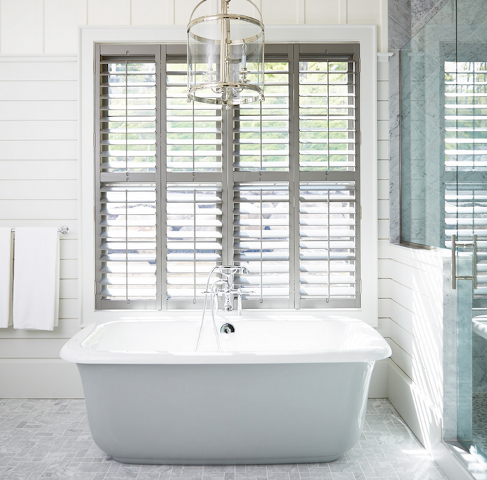 Stunning bathroom features a Round Edwardian Entry lantern suspended over a freestanding tub placed under windows dressed in plantation shutters alongside a grey marble tiled floor next to a shiplap and glass walk in shower.