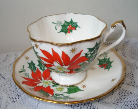 "Queen Anne ""Noel"" teacup and saucer made in England.  Handle is different on this one with gold on top than the stripe look on the edge instead."