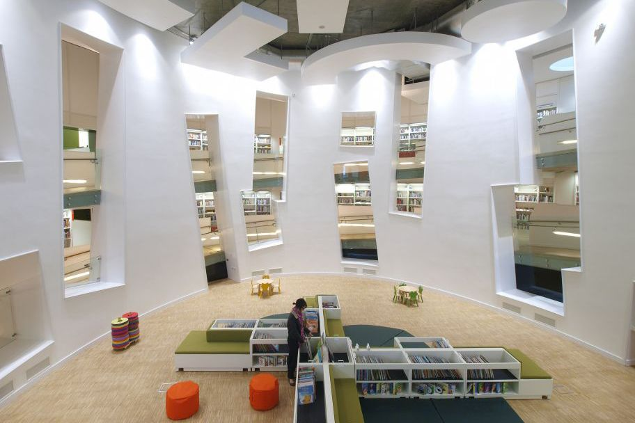 Clapham Library, London. Designed by Studio Egret West. This library is part of a a larger mixed use building complex. It features a ramp lined with 20,000 books that twists around a central atrium. EA.