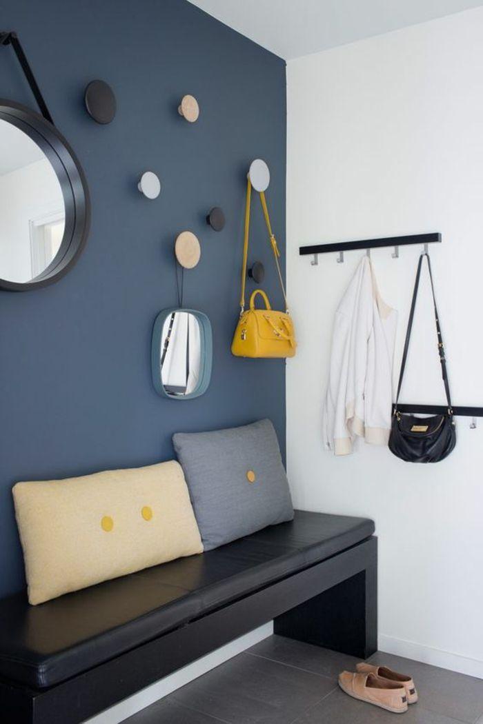 hall d entree maison avec mur en bleu petrole et suspensions rondes multicolores et banc noir tapisse