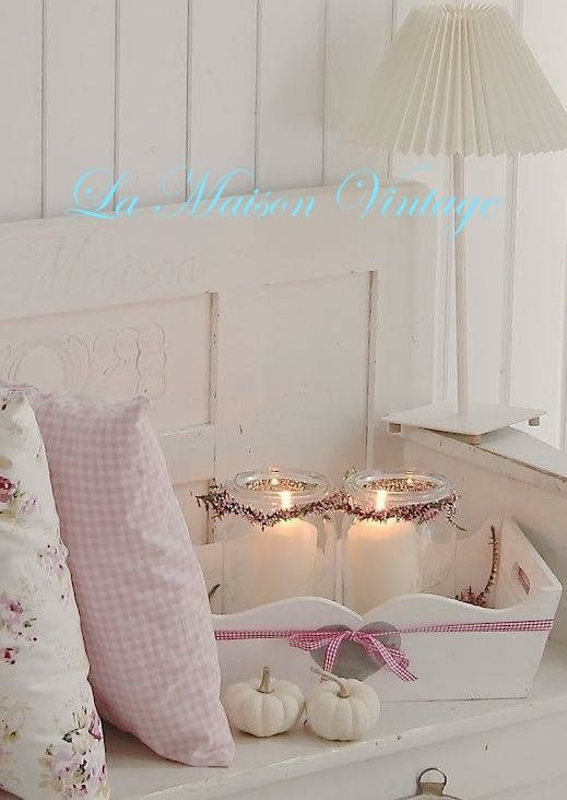 Zarte Einrichtungsidee in Pastell Rosa und Weiß mit Kissen und Windlichtern auf einem Tablett.