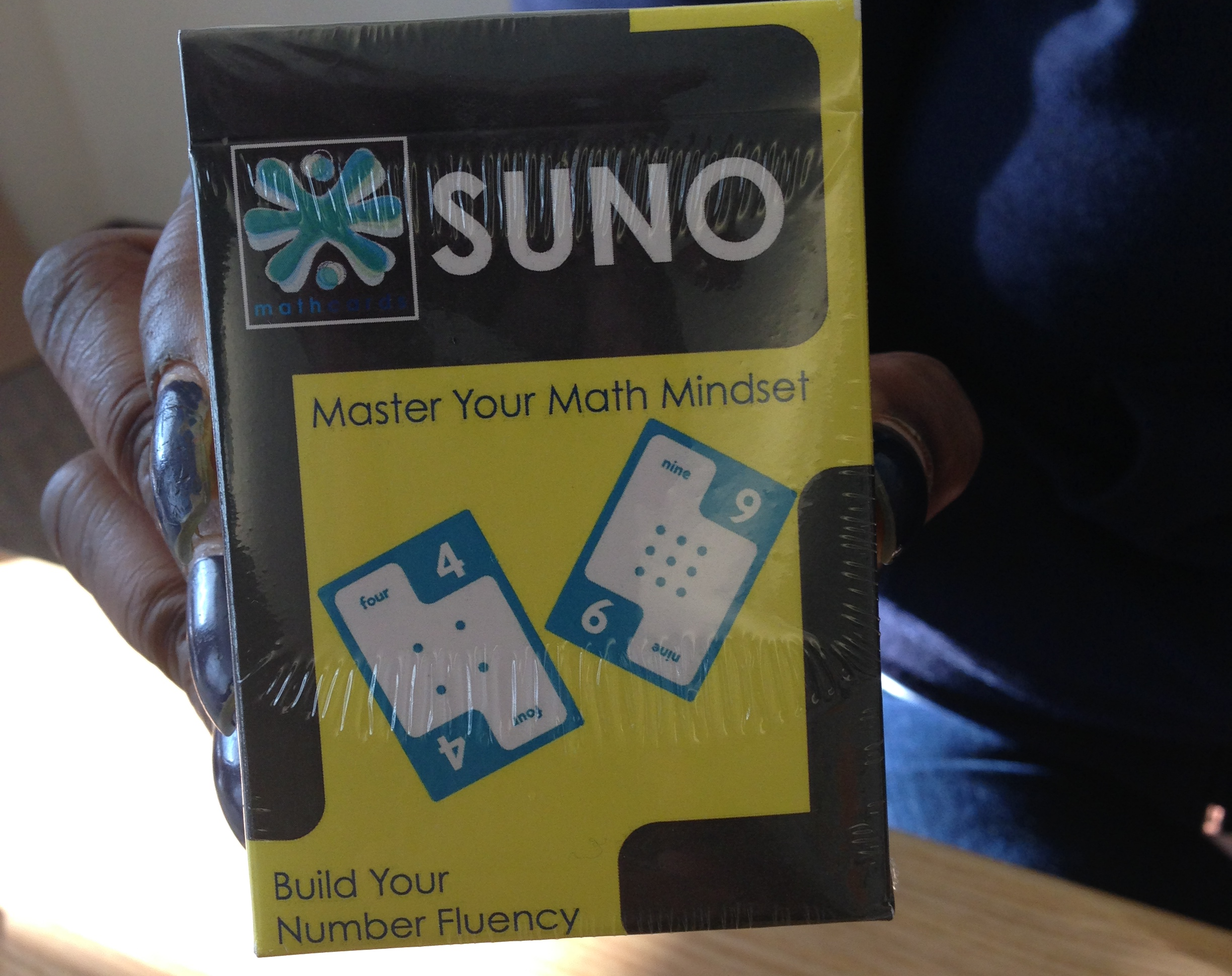 "SUNO - SUNO is a card game (for families and schools) in which players build new and different math sentences using a card from their own hand and a shared card.The objective of the game is to be the first player to get rid of all of ""Your Cards"" – and when you do you will have shutout your opponents and achieved SUNO."
